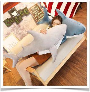 Девушка спит с подушками акулами