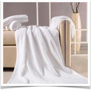 Махровый плед с полотенцами на диване