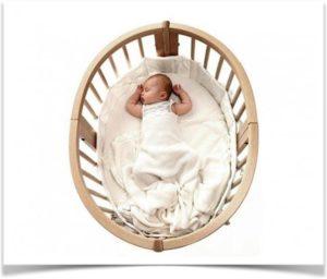 Ребенок спит в овальной деревянной кроватке