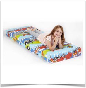 Девочка лежит на разноцветном матрасе