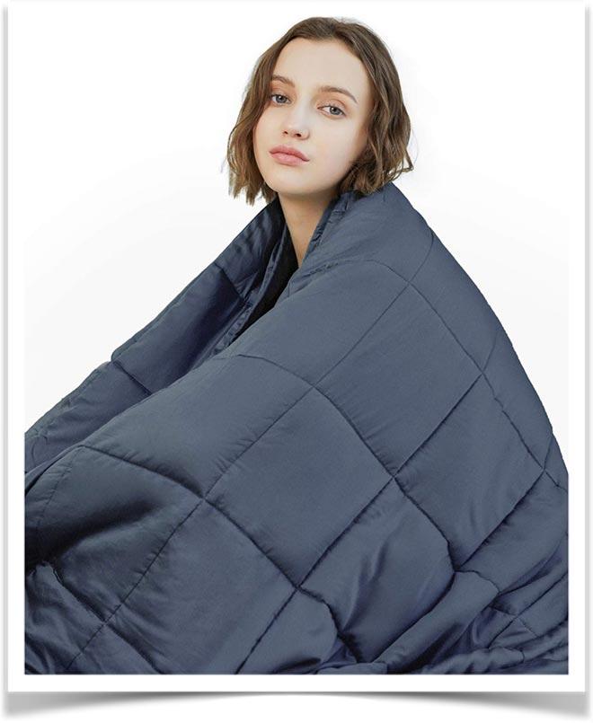 Девушка сидит накрывшись стеганным одеялом