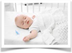 Ребенок в детской кроватке на белом матрасе