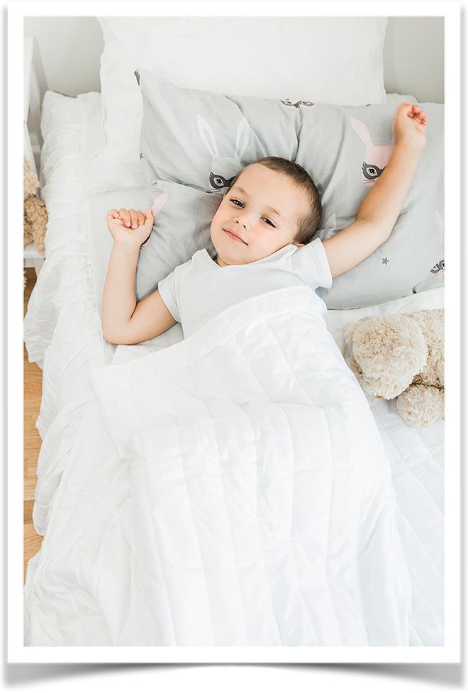 Мальчик растягивает мышцы лежа под одеялом