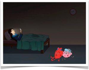 Брюнетка в темной комнате на кровати смотрит в телефон.