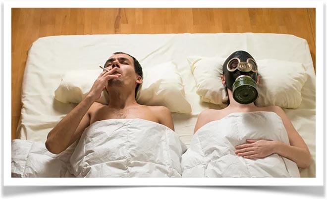 Курящий мужчина и женщина в противогазе лежат на матрасе