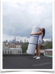 Девушка с запакованным матрасом на крыше дома