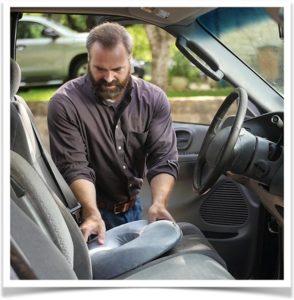 Мужчина кладет на сидение в машине подушку от геморроя