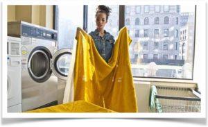 Девушка держит в руках желтое одеяло