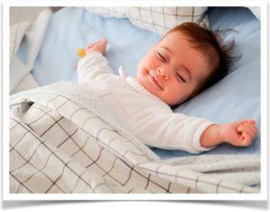 Счастливый ребенок спит в кровати