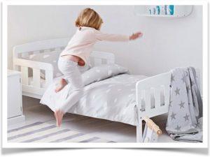 Девочка прыгает на детскую кроватку