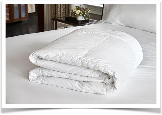 Белое чистое одеяло сложенное на кровати