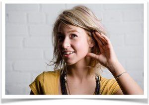 Женщина слушает приложив руку к уху