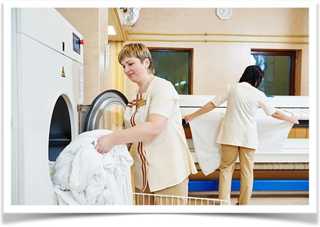 Две женщины работают в прачечной
