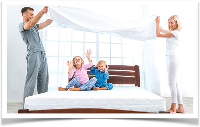 Родители играют с детьми на кровати