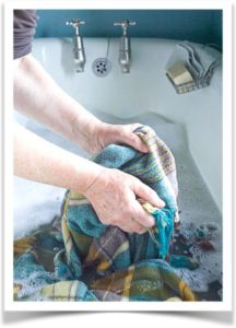 Женщина стирает одеяло руками в ванне