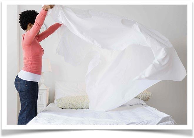Женщина застилает постель