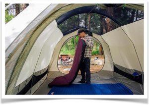 Мужчина надувает матрас в палатке