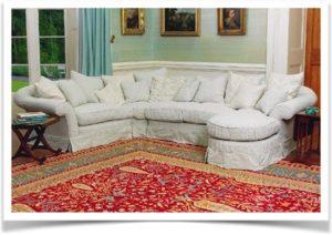 Большой угловой диван на красном ковре