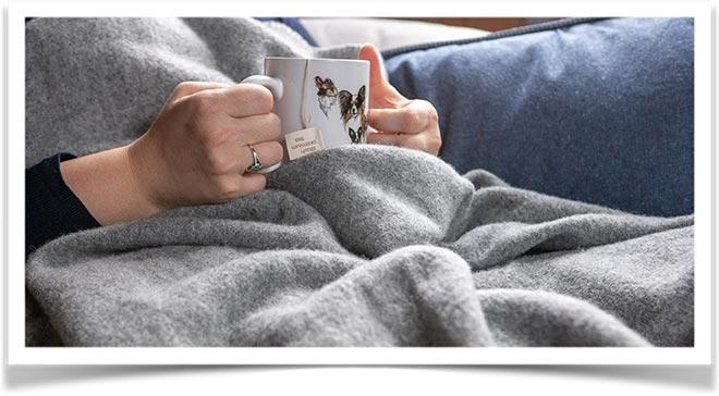 Женщина с кружкой напитка укрылась байковым одеялом